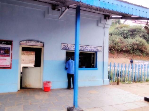Mann am Bahnhofsschalter blauer bahnhof